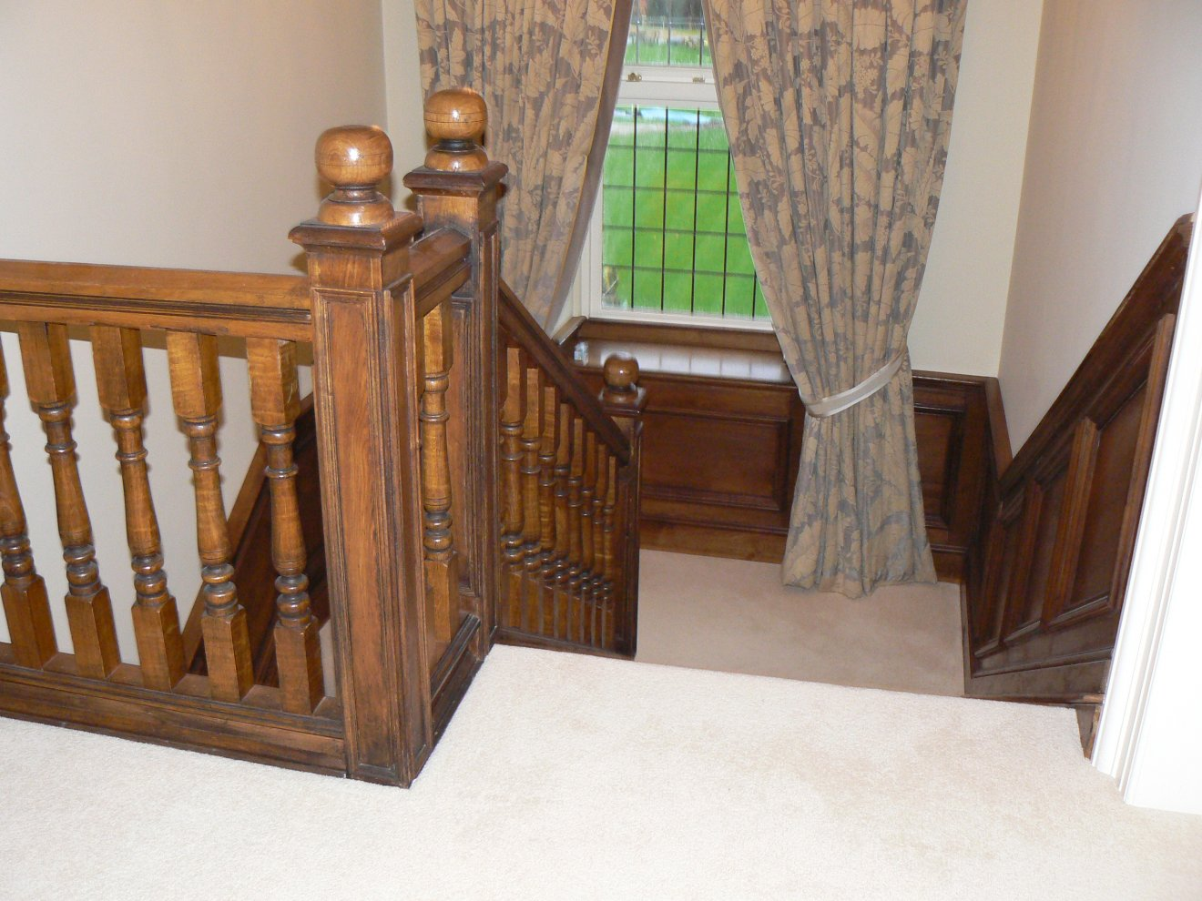 Solid Oak Staircase With Ornate Finials And A Sweeping Handrail
