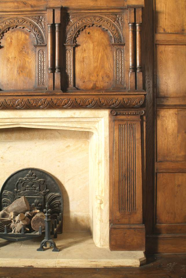 oak overmantel with hand carved arched panels and fluted pilasters