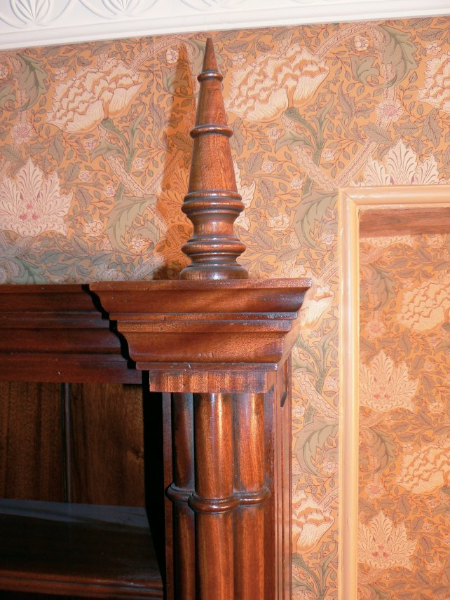 mahogany finial shown against William & Morris wallpaper