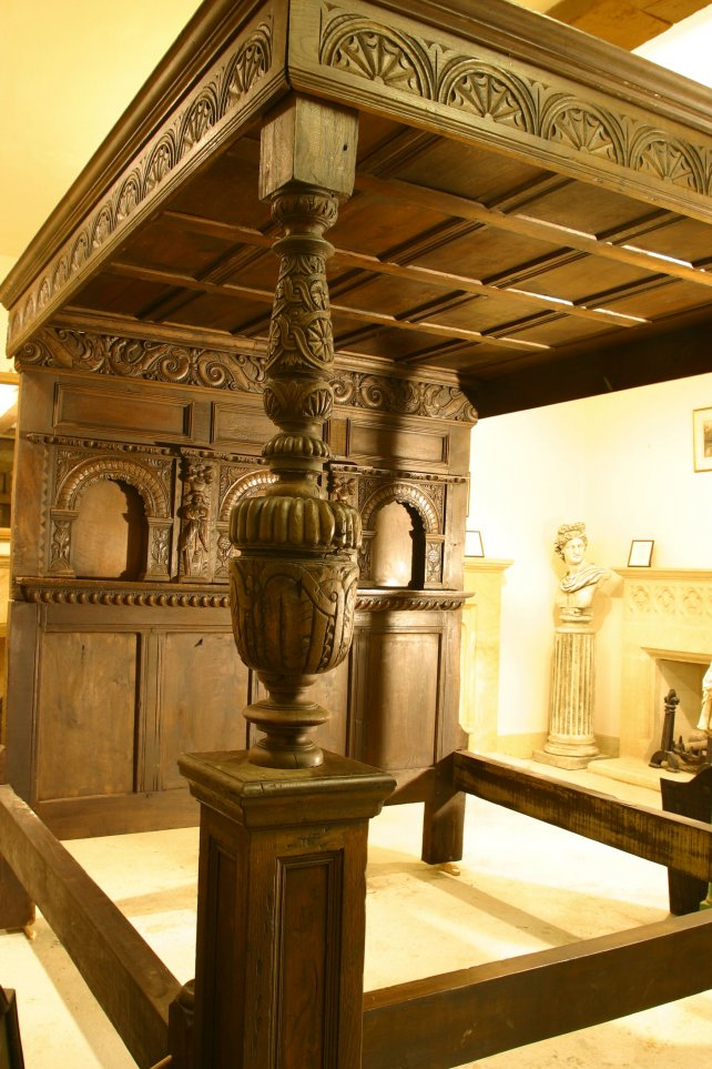 four poster bed with heavily hand carved panels and frieze and bulbous posts
