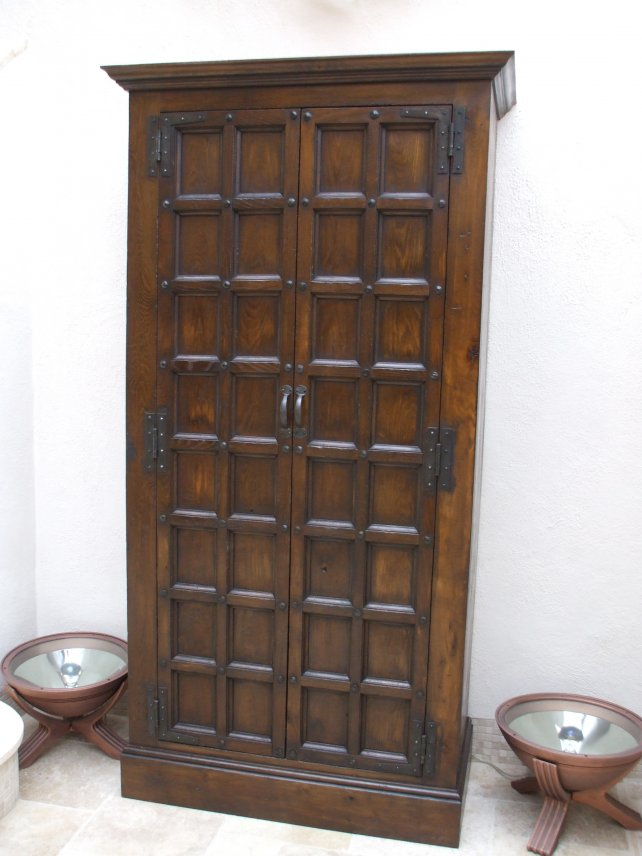 cupboard with small panels and hand carved ironwork
