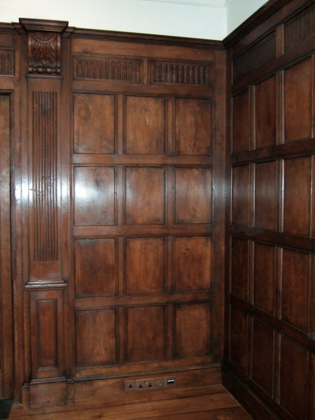 tudor style oak panelled room with fluted pilasters and frieze