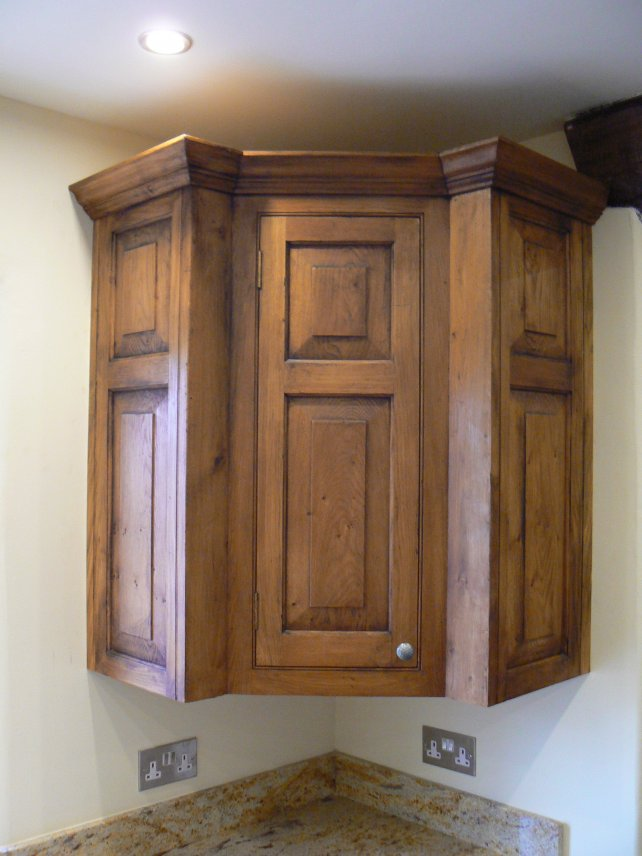 oak corner unit with fielded panels, aged and polished