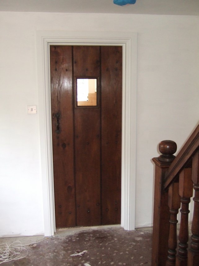 oak planked door with small window and handmade latch