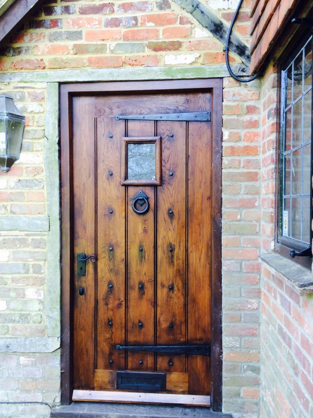 oak framed planked door with small window and handmade ironwork