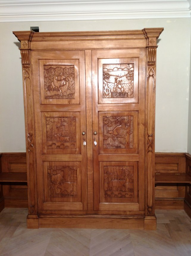 oak gun cabinet with hand carved panels depicting woodland scene