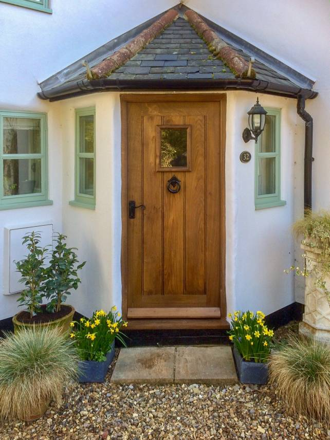 Traditional framed solid oak plank door with tall window