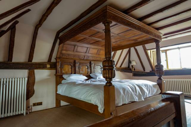 Commissioned carved four poster bed angled to fit the ceiling