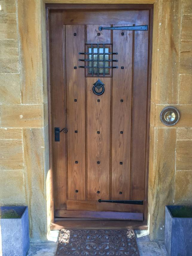 Period front door with metal grill and studs