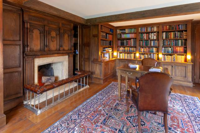 Home study with oak bookcases and carved overmantel