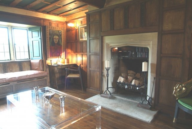 overmantel panelling around stone fireplace and oak flooring