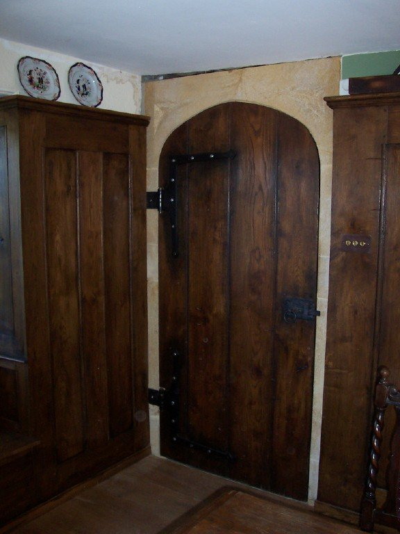 gothic arched planked door with handmade ironwork